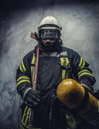 uniform: Bombero de rescate en el casco seguro y uniforme sobre fondo gris. Foto de archivo