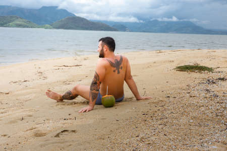 sexual position: Tattooed man relaxing on the beach in tropical country. Stock Photo