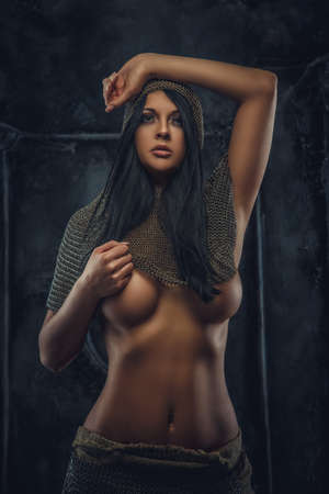 erotic fantasy: Nude portrait of brunette woman in ancient iron clothes and armor.