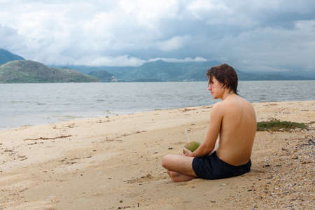 sexual position: Young man relaxing on a beach in Asia. Stock Photo