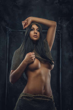 Nude portrait of brunette woman in ancient iron clothes and armor.