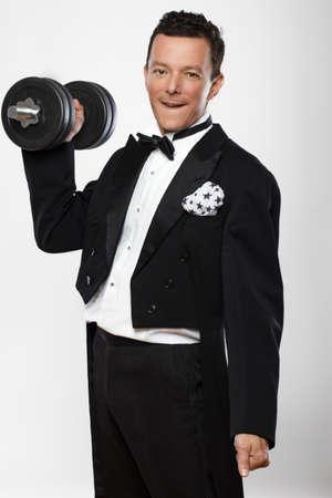 dumbell: Man in tuxedo holds dumbell.