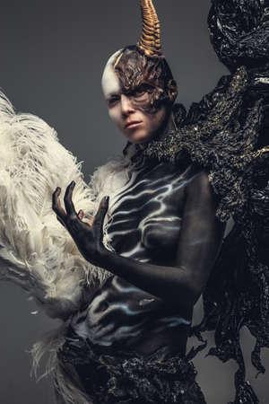 彼女の頭の上の 1 つの角を持つ黒と白の服で悪魔の女性の肖像画。灰色の背景上に分離。 写真素材