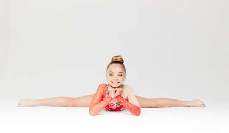 Little girl in red dress doing gymnastic split. Isolated on white background.