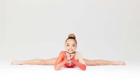 gimnasia ritmica: Niña en vestido rojo que hace fractura gimnástico. Aislado en el fondo blanco. Foto de archivo