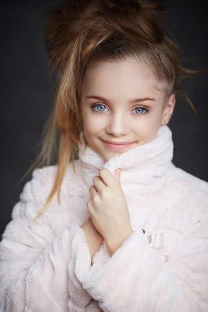 bata blanca: Muchacha del adolescente con maquillaje y corte de pelo posando en bata blanca sobre fondo gris. Foto de archivo