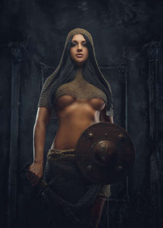 armor: Sexy woman warrior in iron armor holds shield. Stock Photo