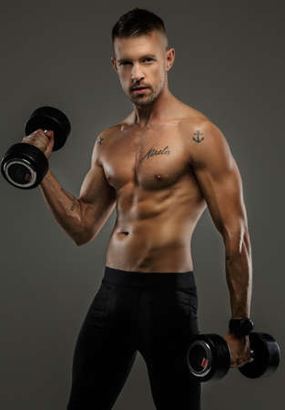 man power: Attractive young man with great muscular body holds dumbells. Isolated on grey background. Stock Photo