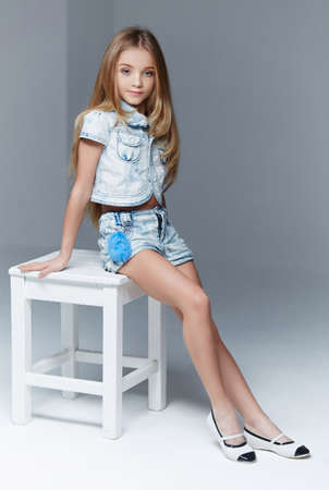 Blond littel girl in shorts and blue shirt posing on white chait in studio.