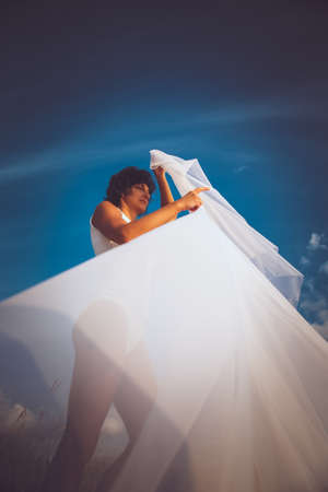 fluttering: Brunette middle age woman in white underwear holding fluttering cloth over blue sky with white clouds.