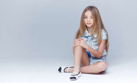 Cute little girl with long blond hair sits on floor in studio. Stock Photo