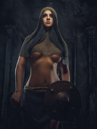 Sexy woman warrior in iron armor holds shield. Stock Photo