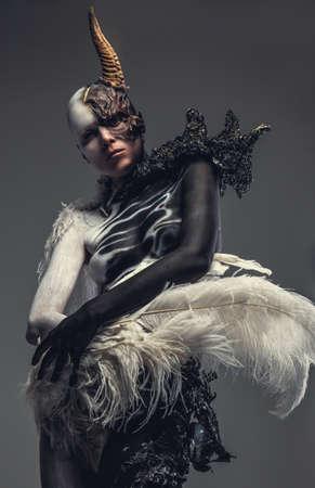 maquillaje fantasia: Retrato de la mujer del diablo vestido de blanco y negro con un cuerno en la cabeza. Aislado en el fondo gris. Foto de archivo