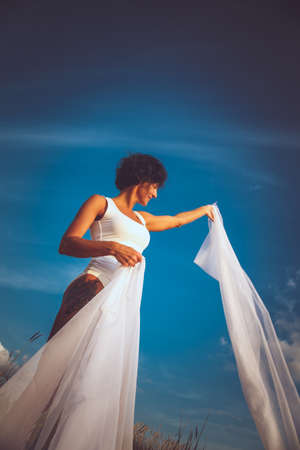 fluttering: Middle age woman in white swimsuit and fluttering white fabric over blue sky.