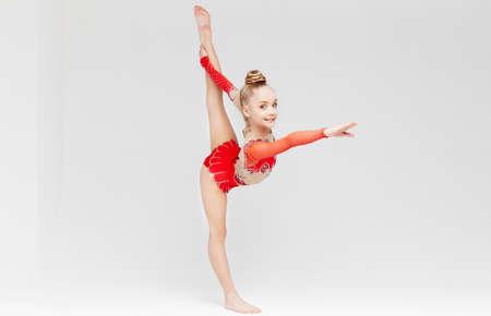 gimnasia ritmica: Niña en vestido rojo que hace fractura de pie sobre fondo blanco.