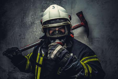 Rescue firefighter in safe helmet and uniform over grey background.