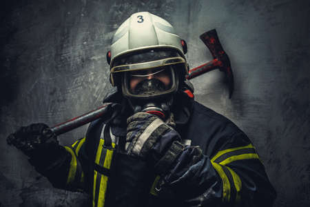bombero: Bombero de rescate en el casco seguro y uniforme sobre fondo gris. Foto de archivo