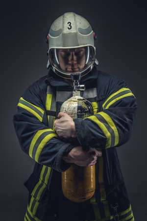 protective suit: Firefighter rescue holds yellow oxygen tank. Isolated on grey background.