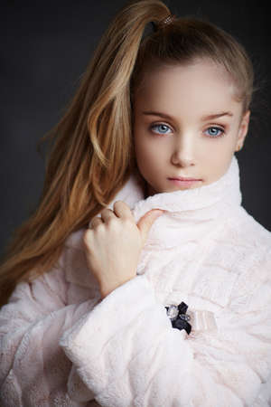 white coat: Teenager girl with make up and haircut posing in white coat over grey background.
