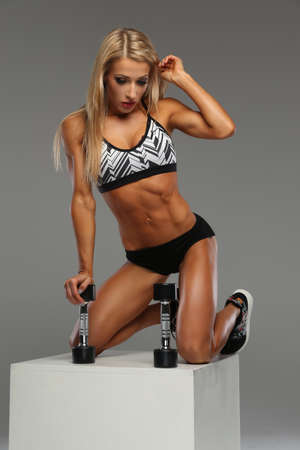 blondy: Blondy slim girl in underwear sits on white box with dumbbells over grey background. Stock Photo