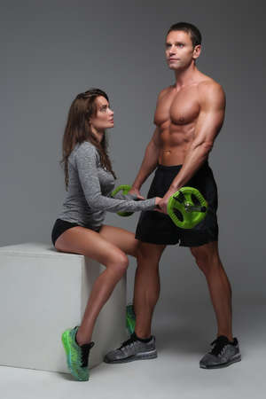 middle age man: Middle age man coaching slim fitness woman with barbell.