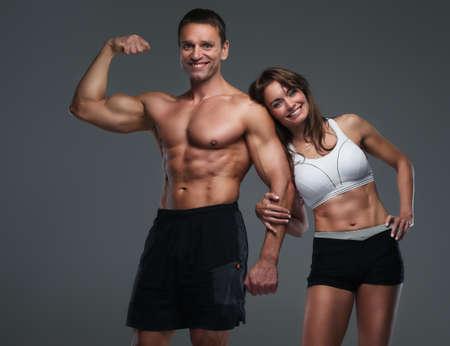 hombre deportista: Individuo positivo sin camisa muscular y delgada mujer atractiva que presenta sobre fondo gris.