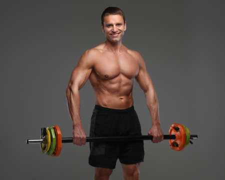 middle age man: Shirtless muscular middle age man doing exercises with colorful barbell.