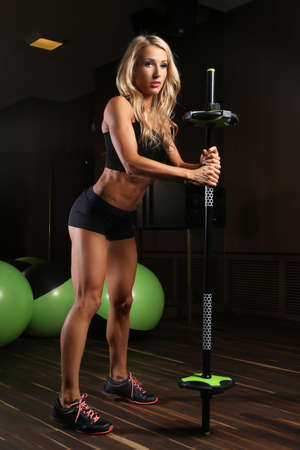 blondy: Blondy athletic female doing exercises with barbell in a gym room with green fitness balls.