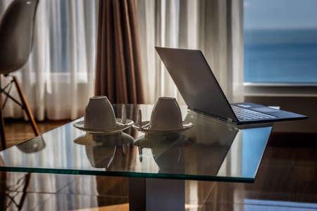 Ordinateur portable mince sur la table en verre dans les appartements modernes.