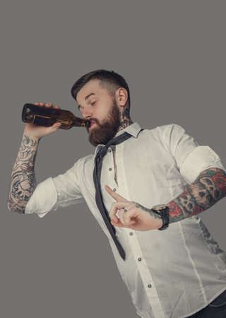tattoed: Tattoed bearded drunk man drinking beer. Isolated on grey background.