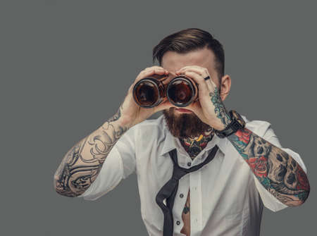 adult tattoo: Man with tattooed arms holds bear bottles like binocular.