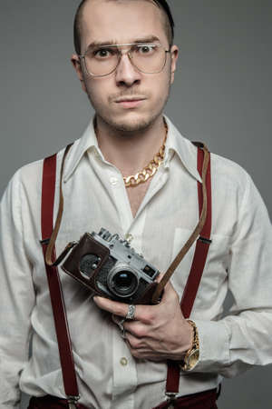 freaky: Freaky guy in sunglasses and white shirt holds film camera over grey background. Stock Photo