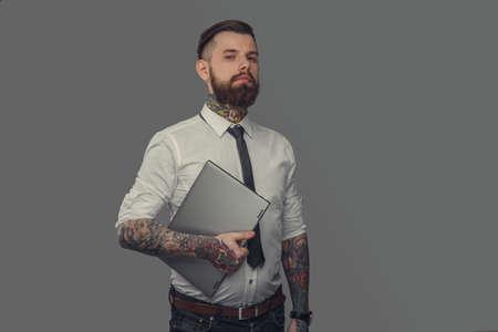 tattoed: Bearded tattoed man in white shirt holding laptop. Isolated on grey background.