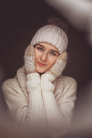 Cute young woman in white sweater and winter hat.