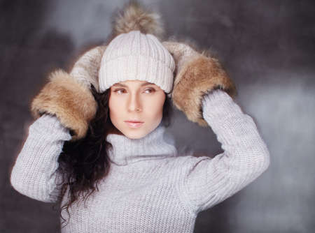 Winter fashion. Woman in winter hat an fur gloves.