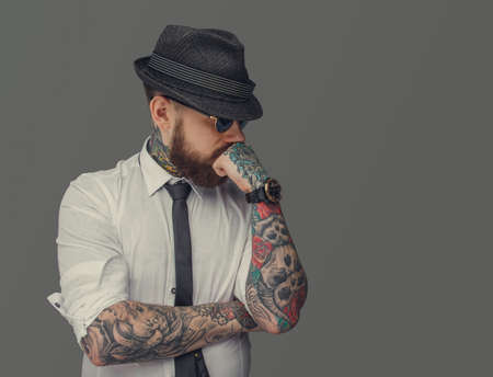 Man with tattooed arms thinking. Isolated on grey background.