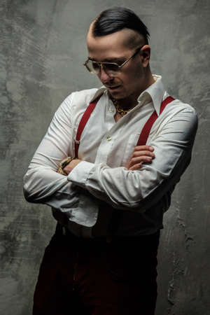 freaky: Freaky man in white shirt and glasses posing over grey wall.
