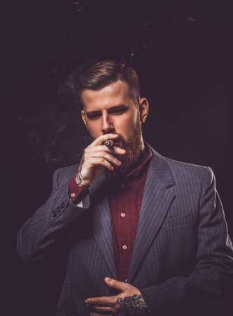cigare: Fashionable bearded man with tattooes smoking cigar.
