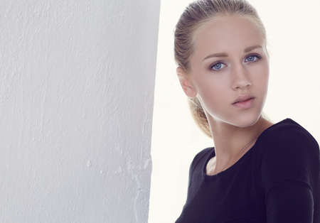 black t shirt: A young woman with blue eyes dressed in black t shirt. Stock Photo