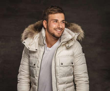 fur hood: Smiling young man in winter warm coat with fur hood.