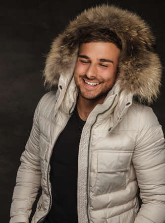 fur hood: Smiling fashionable man in winter white coat with fur hood. Stock Photo