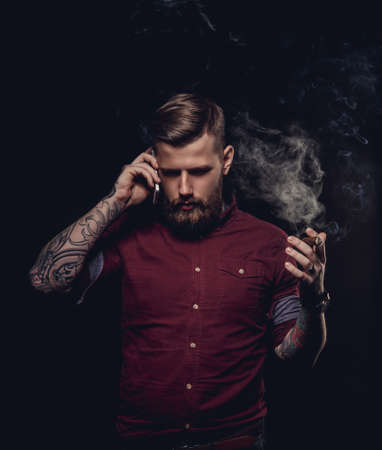 cigare: Stylish man in red shirt smoking cigar and talking by smartphone.