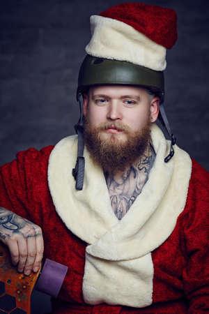 Tattoed bearded man in Santas clothes.