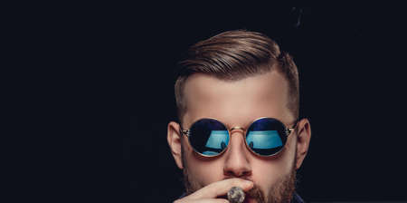 Portrait of bearded man in sunglasses. A man smoking cigare. Isolated on black background.