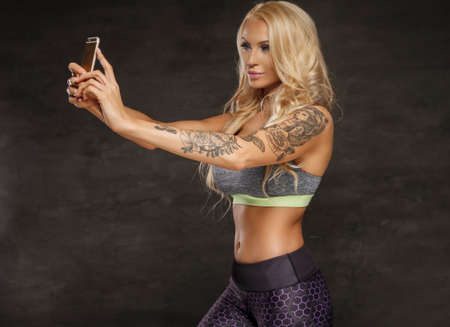 sexy topless woman: Athletic blond woman with tattoo on her arm taking picture by smartphone.