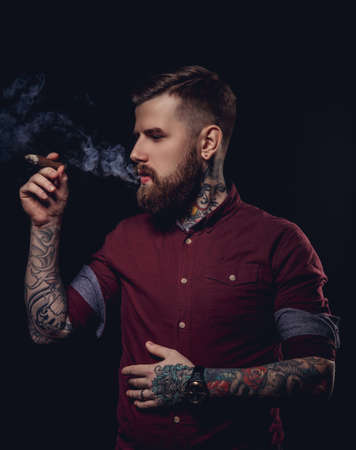 Fashionable bearded man with tattooes smoking cigar.