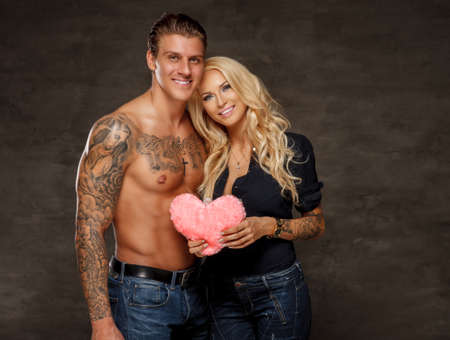 Beautiful couple of shirtless muscular tattooed man and sensual smiling blond woman. Heart in hands. Valentines day