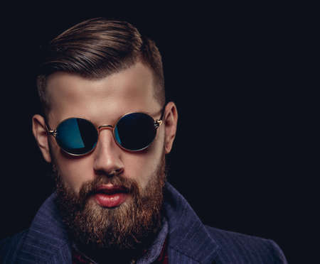 bad guy: Portrait of bearded man in sunglasses. Isolated on black background.