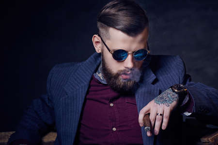 Bearded fashionable man in sunglasses smoking cigar. Stock Photo