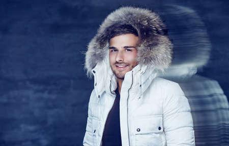 fur hood: Smiling man in warm winter jacket with fur hood. Stock Photo